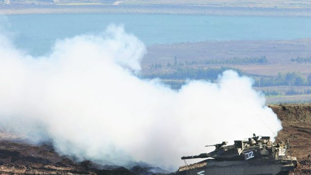 An Israeli tank releases smoke as it maneuvers on the Golan Heights, where tensions with Syria have escalated. getty images