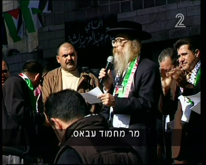 A man from the anti-Zionist Neturei Karta sect addresses a cheering crown in Ramallah's Clock Square (screen capture: Channel 2)