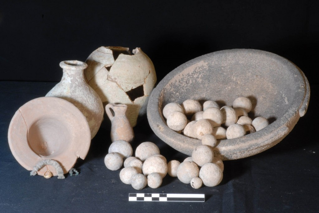 A funerary assemblage with glazed jars, stone weights, bronze fibulae and granulated gold earring from two cremation burials in a pithos in the Outer Town of Karkemish (photo credit: AP Photo/Joint Turco-Italian Archaeological Expedition, File)