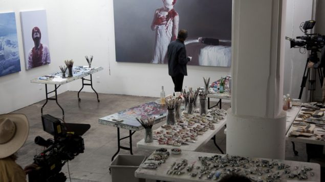 """Gottfried Helnwein painting in his Los Angeles studio, in scene from """"Dreaming Child."""" Courtesy First Run Features"""
