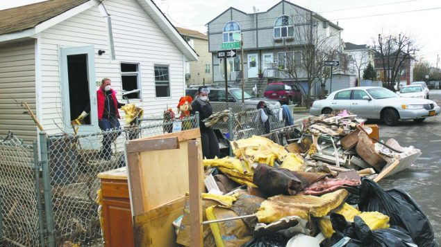 Volunteers remove debris from a damaged home on Staten Island. michael datikash