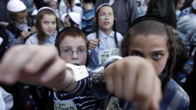 Ultra-Orthodox children wear handcuffs as they protest military conscription in Israel. Getty Images