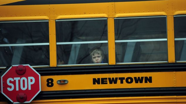 A school bus passes a Newtown church where the funeral of a young Sandy Hook victim is taking place on Dec. 18. Getty Images