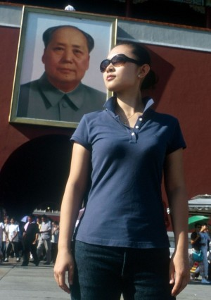 A Chinese woman next to a large poster of Mao Zedong, founding father of the People's Republic, on Tiananmen Square in Beijing. (Photo credit: Serge Attal/FLASH90)