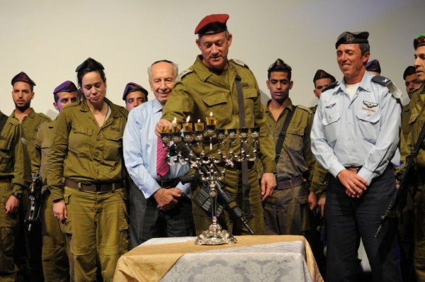 Chief of the General Staff Lt. Gen. Benny Gantz, flanked by President Shimon Peres (left) and IDF Chief Rabbi Brig. Gen. Rafi Peretz (right), lighting a menorah this week (photo credit: IDF Spokesman's Office/Flash 90)