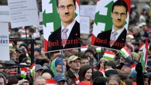 Portrait of Hungarian lawmaker of the Jobbik party, Marton Gyongyosi (depicted with a Hitler mustache), at the protest called Mass Demonstration Against Nazism in front of the Parliament building in Budapest, Hungary, Sunday, December 2 (photo credit: AP/MTI, Laszlo Beliczay)