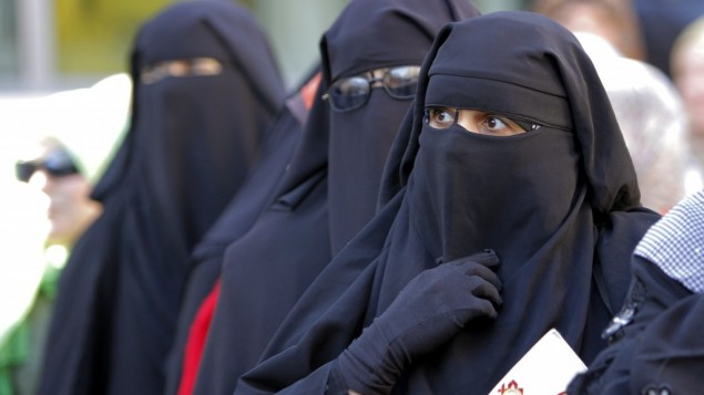 Egyptian women wearing niqab coverings line up outside a polling station to vote in the second round of a referendum in Giza, Egypt, on Saturday. (photo credit: AP/Amr Nabil)