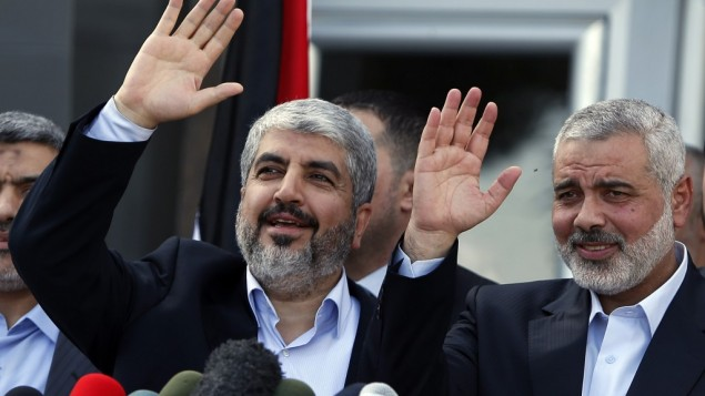 Exiled Hamas chief Khaled Mashaal, left, and Gaza's Hamas Prime Minister Ismail Haniyeh wave during a news conference upon Mashaal's arrival in the Gaza Strip on December 7. (photo credit: AP/Suhaib Salem, Pool)