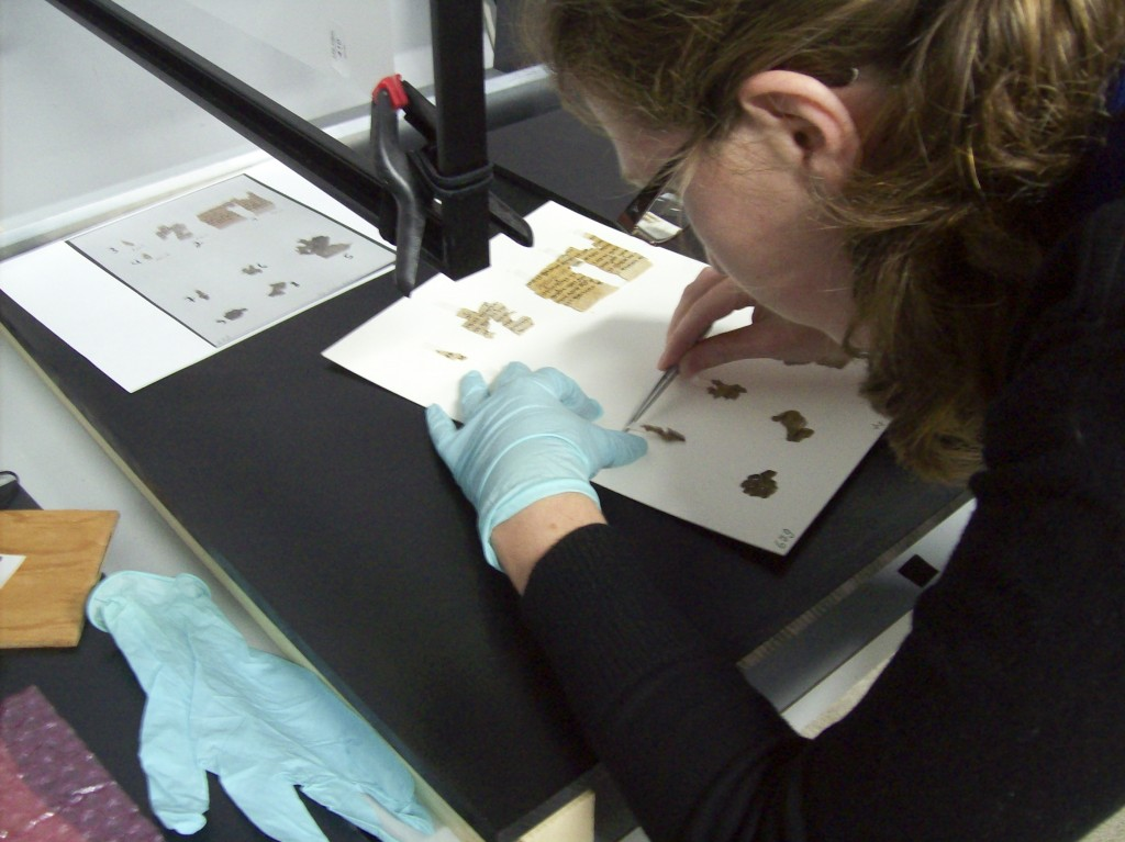 An IAA conservator working on scroll fragments (Photo credit: Shai Halevy/Israel Antiquities Authority)