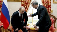 Russian President Vladimir Putin, left, sits down as Turkey's Prime Minister Recep Tayyip Erdogan looks on before a meeting in Istanbul, Turkey, Monday, Dec. 3, 2012.  (photo credit: AP/Tolga Bozoglu, Pool)