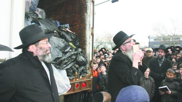 Rabbi Zevi Trenk kisses a damaged holy book before it is shipped for burial. Courtesy Darchei Torah