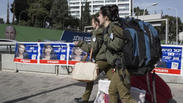 Soldiers pass by campaign posters of Labor party leader Sheli Ehimovitch ahead of Israel's Jan. 22 elections. Getty Images