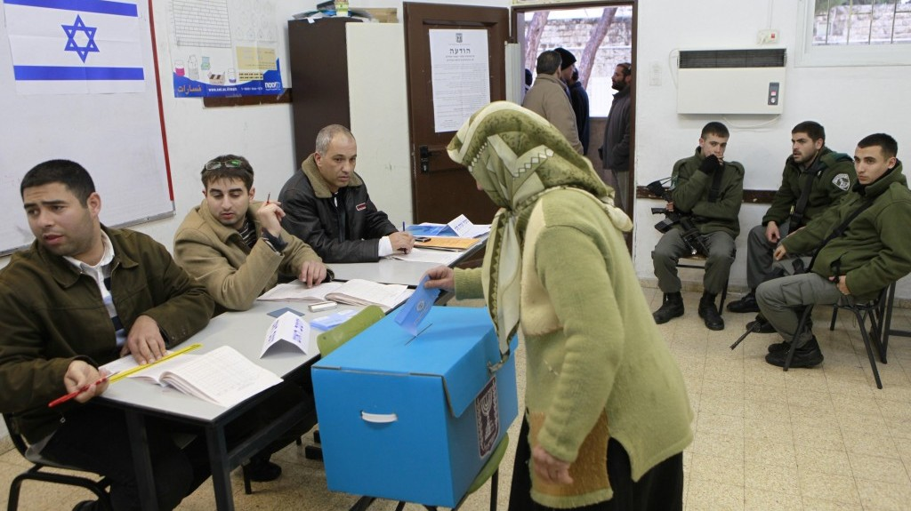 An Arab Israeli woman casts her vote as Israeli border policemen look on at a polling station in the Arab village of Abu Gosh, west of Jerusalem, on February 10, 2009 (photo credit: Nati Shohat/Flash90)