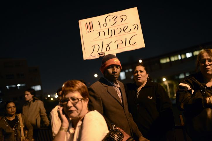 Protesters hold up a sign that reads 'Help! The neighborhoods are sinking,' at an anti-migrant demonstration in Tel Aviv, Monday, December 31 (photo credit: Tomer Neuberg/Flash90)