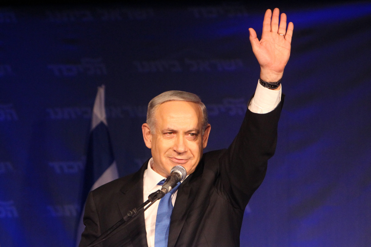 Prime Minister Benjamin Netanyahu waves to supporters after initial election results early Wednesday showed the Likud-Beytenu heading for a victory, albeit with a much-reduced number of Knesset seats (photo credit: Miriam Alster/Flash90)