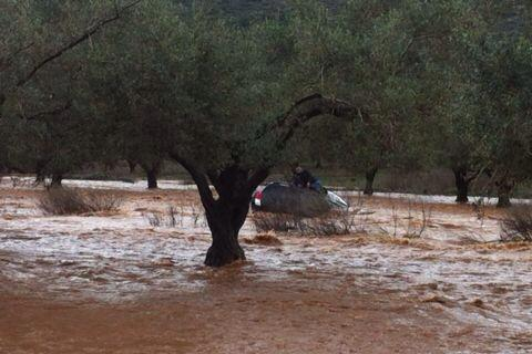 Driver whose car was swept away by the Hilazon stream sits on the top of the vehicle while waiting for rescue workers to arrive (photo credit: Israel Police via Facebook)