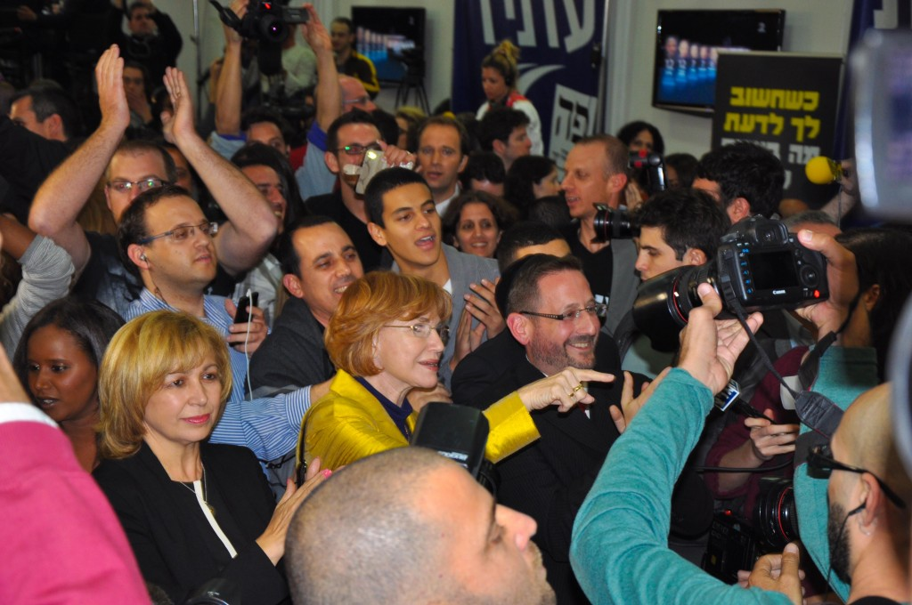 Ecstatic scenes at Yesh Atid's headquarters Tuesday night as the TV exit polls are broadcast, with putative MK Dov Lipman, bearded with kippa, at center (photo credit: Michal Shmulovich)