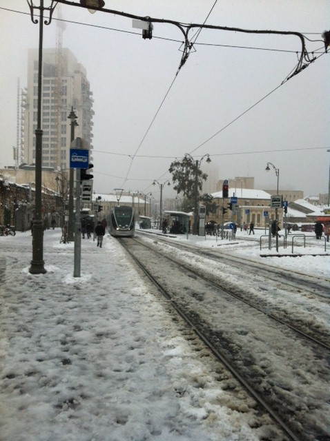 A light rail arrives at the slush-covered Mahane Yehuda stop. (photo credit: Greg Tepper/Times of Israel staff)