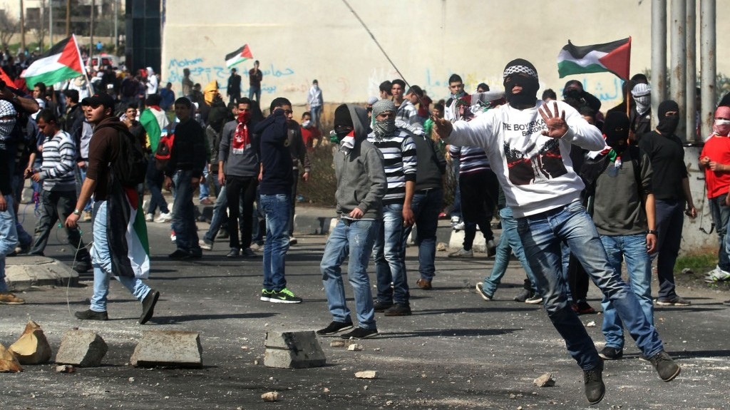 Palestinian protesters hurl rocks at Israeli soldiers during clashes next to Ofer prison, near the West Bank city of Ramallah, on Thursday (photo credit: Issam Rimawi/Flash90)