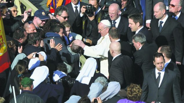 Common touch: Pope Francis greets well-wishers, including a disabled boy, in Rome Tuesday. getty images