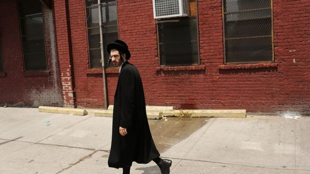 An Orthodox Jew strolls by some coveted Brooklyn real estate. Getty Images