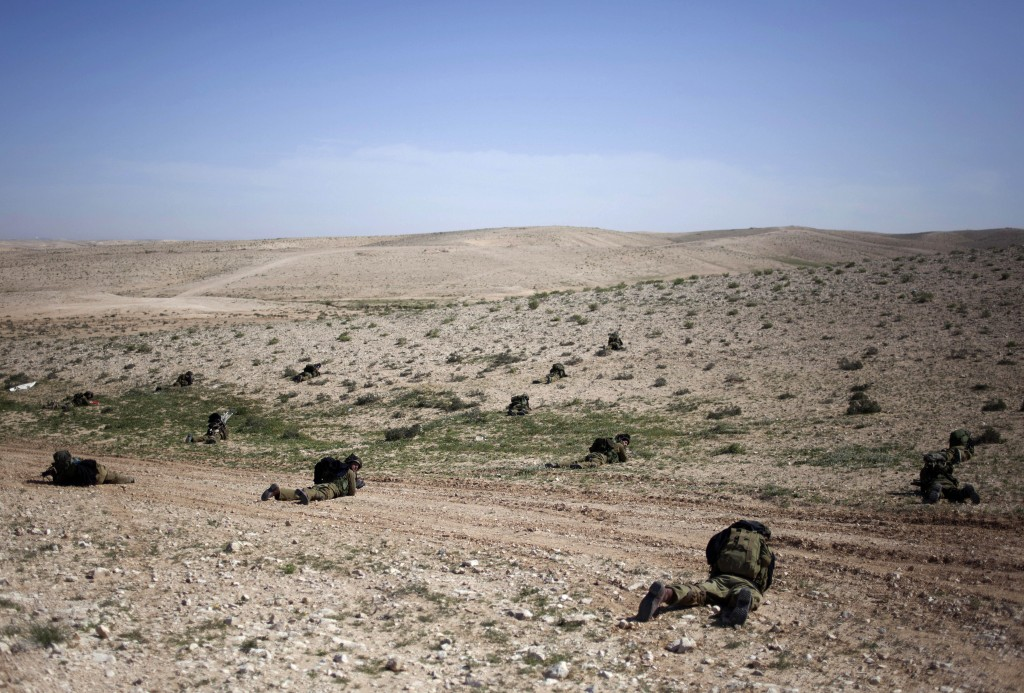 Israeli soldiers lay on the ground as they participate in a drill near Revivim, southern Israel, Thursday, March 7, 2013 (photo credit: AP/Sebastian Scheiner)