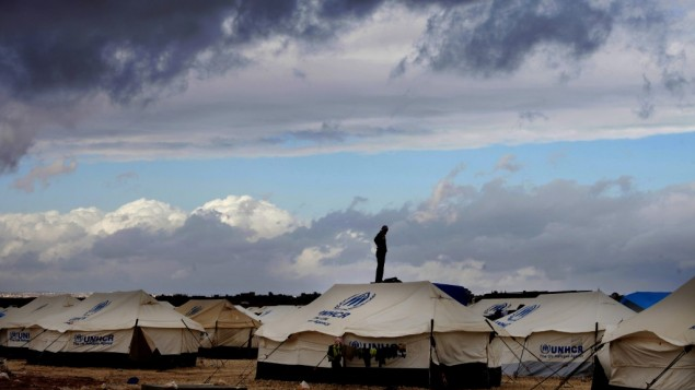 A Syrian refugee stands on top of a water tank at the Zaatari refugee camp, near the Syrian border in Mafraq, Jordan, in January (photo credit: AP/Mohammad Hannon)