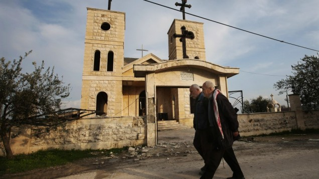 In this Thursday, Feb. 21, 2013 photo, Syrian citizens walk in front of a church that was shelled by mortars, at the Christian village of Judeida, in Idlib province, Syria (photo credit: AP/Hussein Malla)