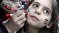 In this citizen journalism image provided by Aleppo Media Center AMC which has been authenticated based on its contents and other AP reporting, Syrian girls paint their faces with colors of the Syrian revolutionary flag during a fesitval, in Aleppo, Syria, Wednesday March 20, 2013 (photo credit: AP/Aleppo Media Center)