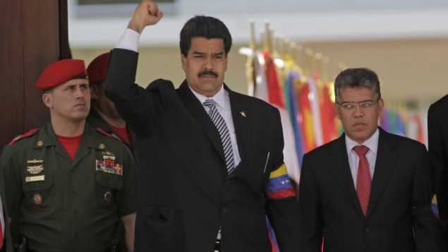 Venezuela's Vice President Nicolas Maduro raises his fist as he arrives along with Foreign Minister Elias Jaua, right, for the funeral ceremony for Venezuela's late President Hugo Chavez at the military academy in Caracas, Venezuela, Friday, March 8 (photo credit: AP/Rodrigo Abd)