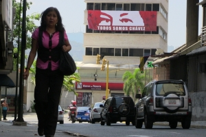 A pedestrian walking underneath a poster showing the eyes of the late leftist leader Hugo Chavez in downtown Caracas. JTA
