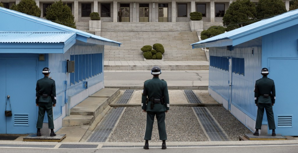 A North Korean soldier, center top, looks at the southern side as South Korean soldiers stand guard at the border village of Panmunjom, which has separated the two Koreas since the Korean War, in Paju, north of Seoul, South Korea, Wednesday, April 10, 2013.