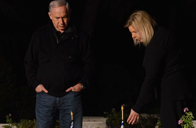 Prime Minister Benjamin Netanyahu and his wife, Sara, seen next to the grave of Netanyahu's late brother Yoni at the Mt Herzl military cemetery in Jerusalem, Saturday, April 13, 2013 (photo credit: Kobi Gideon/Flash90)