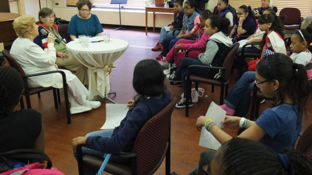 Marion Sacher, left at table, and Pearl Brown, center, relate their wartime experiences to students from a Bronx public school.