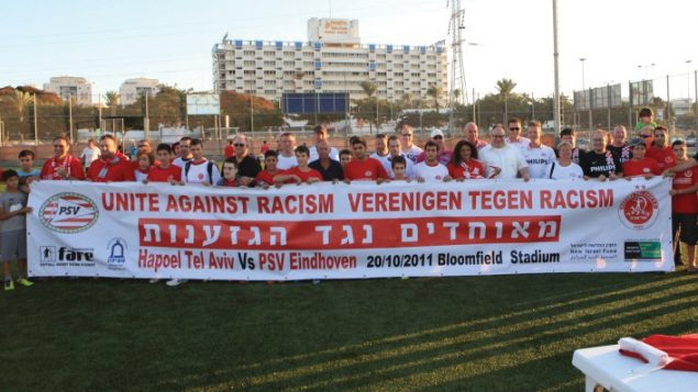 "Israeli and Dutch Soccer fans carrying a sign reading ""fans against racism"" at an event in Tel Aviv, 2011. JTA"