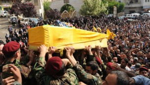 Hezbollah fighters in their military uniform, foreground, carry the coffin of Hezbollah fighter Hassan Faisal Shuker, 18, who was killed in a battle against Syrian rebels in the Syrian town of Qusair on Monday May 20 (photo credit: AP)