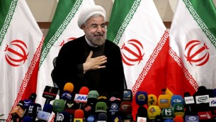 Iran's newly elected president Hasan Rowhani places his hand on his heart as a sign of respect, after speaking at a press conference, in Tehran, Monday, June 17, 2013. (Photo credit:AP/Ebrahim Noroozi)