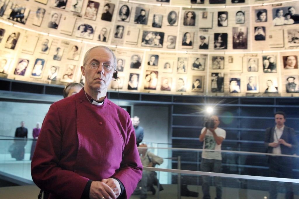 Archbishop of Canterbury and senior bishop in the Church of England Justin Welby looks at photographs of individual Holocaust victims in the Hall of Names at the Yad Vashem Holocaust Memorial museum in Jerusalem, Thursday, June 27, 2013 (photo credit: Photo by Isaac Harari/Flash90)