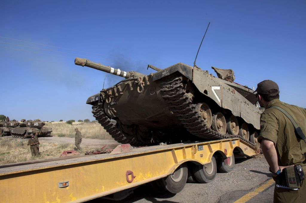 An Israeli tank is loaded onto a truck near the Quneitra crossing with