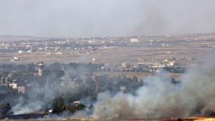 Smoke rises from a fire as a result of fighting in the Syrian village of Quneitra near the border with Israel, as seen from an observatory near the Quneitra crossing, Thursday, June 6 (photo credit: AP/Sebastian Scheiner)