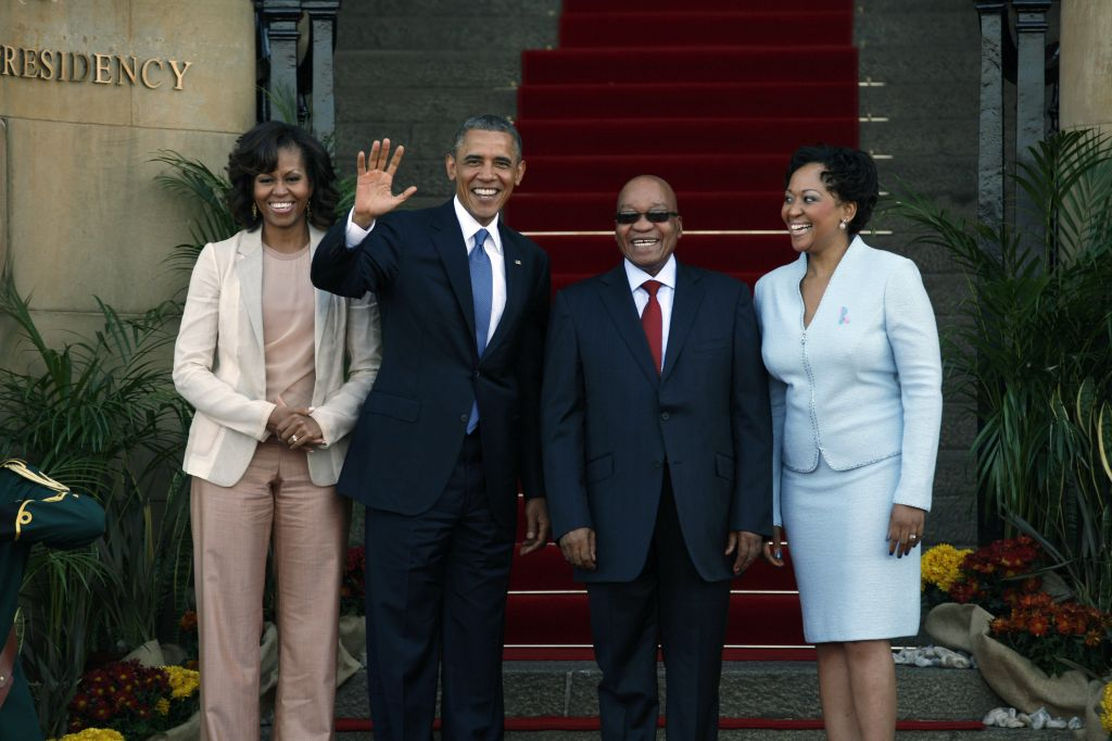 Obama flanked by First Lady Michelle Obama, left, waves with South