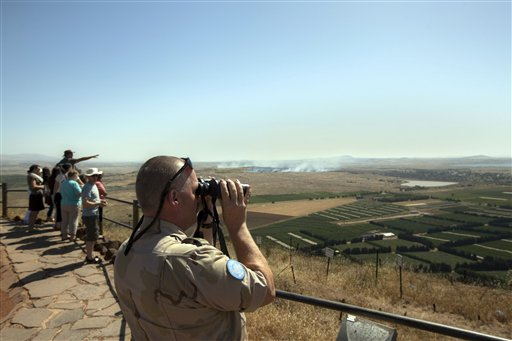 A UN soldier looks through binoculars towards Syria from an observation point on Mt. Bental in the Golan Heights, near the border between the Golan Heights and Syria, Friday, June 7, 2013 (photo credit: AP Photo/Sebastian Scheiner)