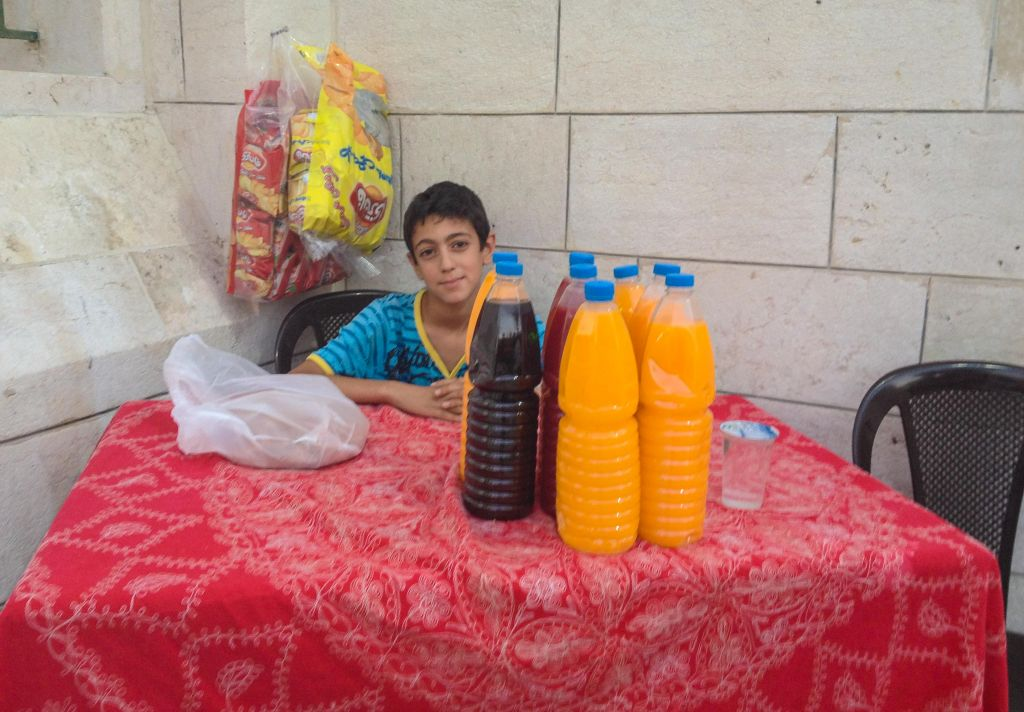 A young Ammani sets up a juice stand outside a mosque for people to break their fast with (photo credit: Michal Shmulovich/Times of Israel)