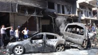Syrian citizens gather near damaged cars that were burned after a car bomb exploded in the suburb of Jaramana, Damascus, Syria, on Thursday, July 25, 2013. (photo credit: AP Photo/SANA)