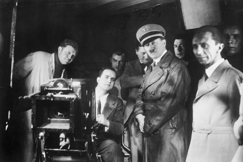 Hitler, Goebbels and others watch filming at Universum Film AG, the principal film studio in Germany at the time, 1935.(Photo credit: CC-BY-SA, Bundesarchiv, Bild 183-1990-1002-500, Wikipedia)