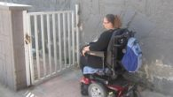 Naomi Moravia, Struggle for the Disabled, in front of a locked gate that leads to a bomb shelter. Ben Sales