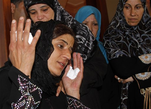 Siham, wife of Mohammed Darrar Jammo, a Syrian political analyst and one of Syrian President Bashar Assad's strongest defenders who was gunned down inside his home, mourns her husband, in the southern coastal town of Sarafand, Lebanon, Wednesday, July 17, 2013 (photo credit: AP Photo/Mohammed Zaatari, File)