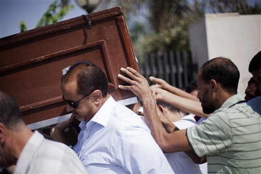 Friends and relatives of Ammar Badie, 38, killed Friday by Egyptian security forces during clashes in Ramses Square, and also son of Muslim Brotherhood's spiritual leader Mohammed Badie, carry his coffin during his fune