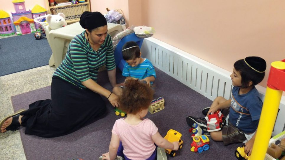 Orna Davidov plays with a group of children in home-based daycare program in Kew Gardens Hills. MIchael Datikash