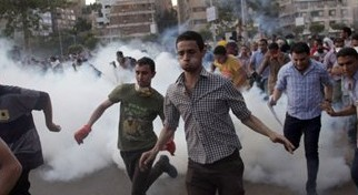 Supporters of Egypt's ousted president Mohammed Morsi run for cover from tear gas fired by police (not seen), during a protest in Cairo, Egypt, on Friday, August 30, 2013. (photo credit: AP/Khalil Hamra)